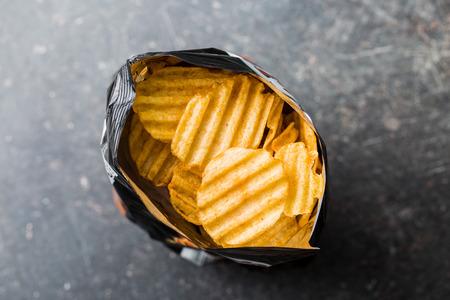 Crinkle croustilles coupées sur la table de la cuisine. Tasty chips épicées dans un sac. Vue de dessus.
