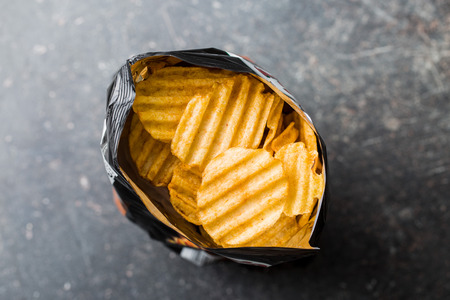 snacks: Crinkle cut potato chips on kitchen table. Tasty spicy potato chips in bag. Top view. Stock Photo