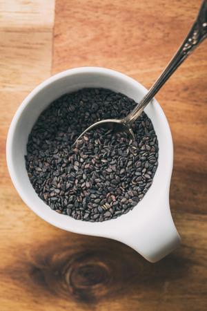 ajonjoli: Semillas de sésamo negro. semillas de sésamo saludables en un tazón en la mesa de madera. Vista superior.