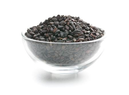 ajonjoli: Semillas de sésamo negro. semillas de sésamo saludables en un tazón aisladas sobre fondo blanco. Foto de archivo