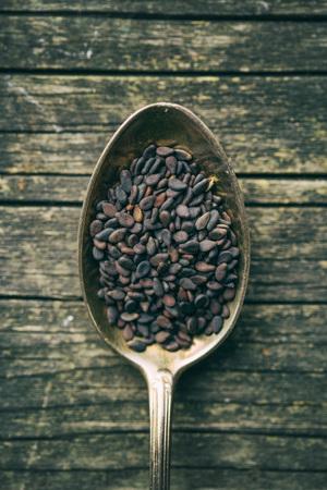 black sesame: Black sesame seeds. Healthy sesame seeds in spoon on wooden table. Top view.