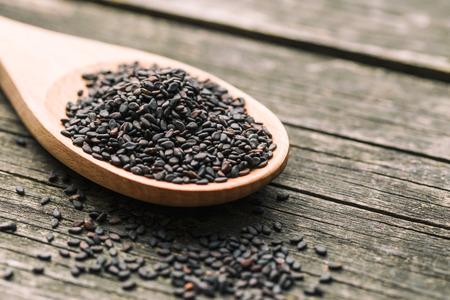 黒ゴマ。木製のテーブルのスプーンで健康的な胡麻。