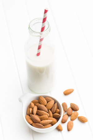almond: Almond milk and almonds. Tasty milk in glass bottle. Stock Photo