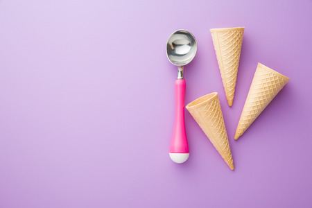 tube top: wafer cone and ice cream scoop on violet background. Top view.