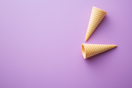 Sweet wafer cones on violet background.