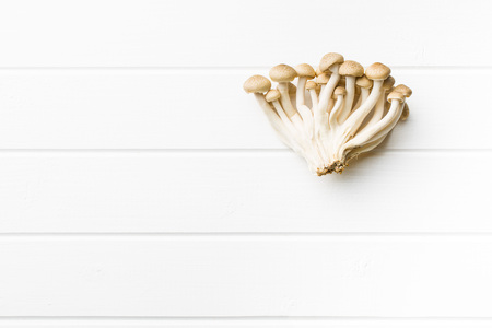 breech: Brown shimeji mushrooms. Healthy superfood on white table. Stock Photo