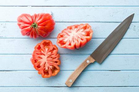 beefsteak: Coeur De Boeuf. Beefsteak tomatoes and knife on kitchen table.