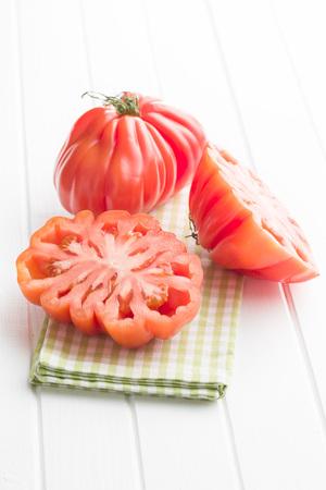 coeur: Coeur De Boeuf. Beefsteak tomatoes on white table.
