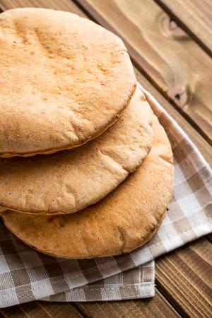 pita: Tasty pita bread on old wooden table.