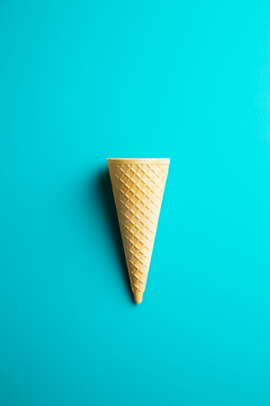 Sweet wafer cone on color background. Top view.