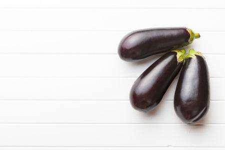 white kitchen: tasty fresh eggplants on white kitchen table Stock Photo