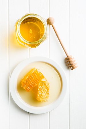 Fresh honey with honeycomb on kitchen table. Banque d'images
