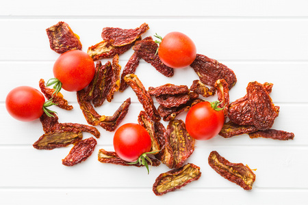Fresh and dried tomatoes on white table.