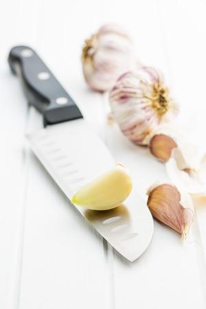 spiciness: The peeled garlic on knife. Stock Photo