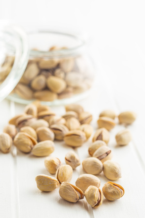 hard core: The pistachio nuts on white table.