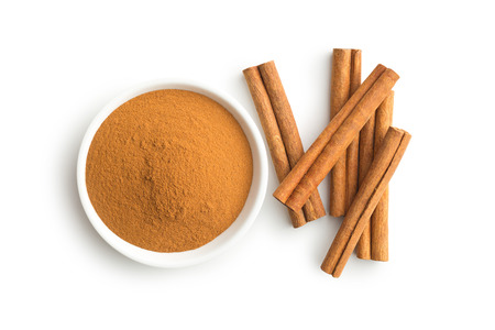 Cinnamon sticks and ground cinnamon isolated on white background. Top view. Stock Photo