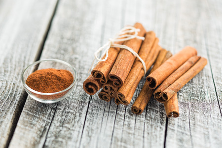 Cinnamon sticks and ground cinnamon on old wooden table. Banco de Imagens