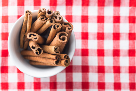 cinnamon stick: Cinnamon stick in bowl on checkered tablecloth. Top view.