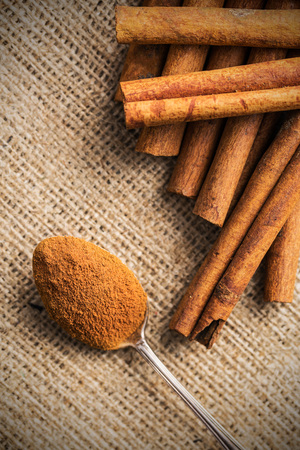 Cinnamon stick and ground cinnamon in spoon. Top view.