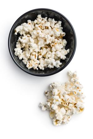 Leckere gesalzen Popcorn in der Schüssel getrennt auf weißem Hintergrund.