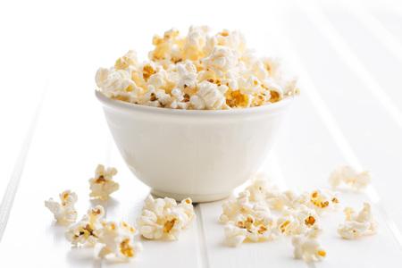bowl of popcorn: popcorn in bowl on white table