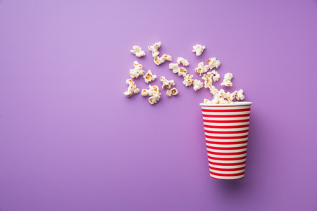 Popcorn in paper cup on colorful background. 免版税图像