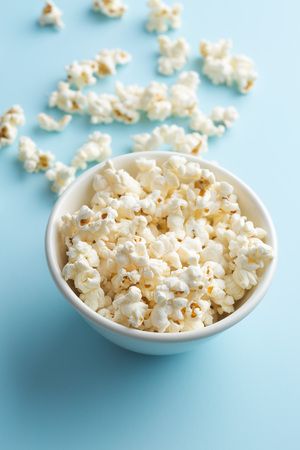 bowl of popcorn: Popcorn in bowl on blue background.