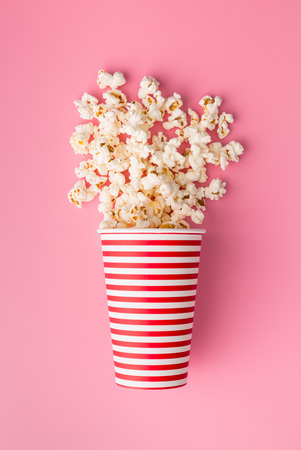 Popcorn in paper cup on colorful background. Foto de archivo