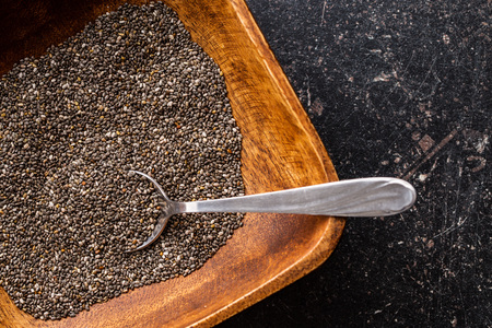 super macro: Chia seeds in wooden bowl. Top view. Healthy superfood.