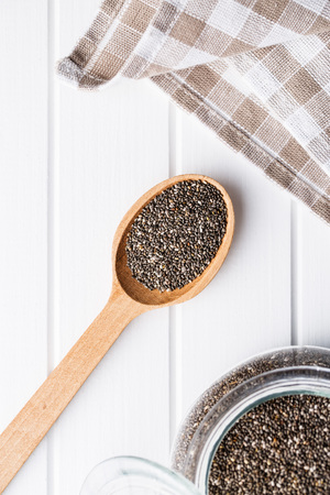 Chia seeds in wooden spoon. Top view. Healthy superfood.