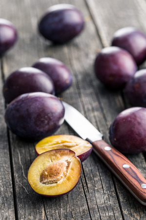 halved: Halved ripe plums and knife on old wooden table.