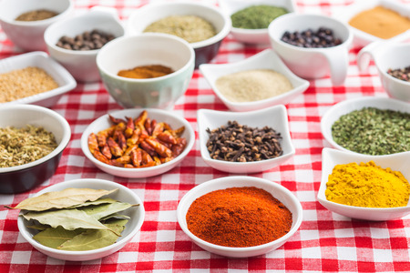 dried herbs: Various dried herbs and spices on checkered tablecloth.
