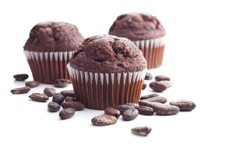 magdalenas: Los sabrosos muffins de chocolate y cacao en grano aislado en el fondo blanco.