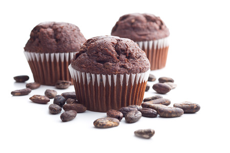 The tasty chocolate muffin and cocoa beans isolated on white background.