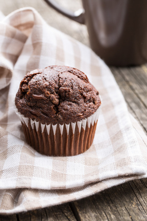 muffin: The tasty chocolate muffins on old wooden table.