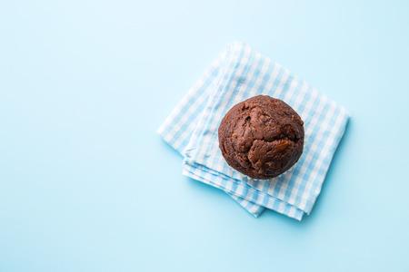 青のナプキンにおいしいチョコレートのマフィン。平面図です。 写真素材