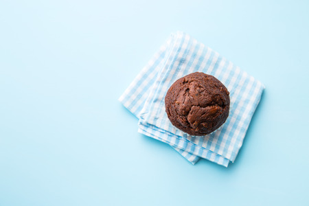 The tasty chocolate muffin on blue napkin. Top view.