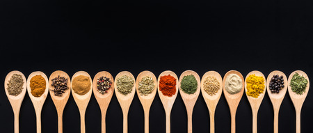 Various spices in wooden spoons on black background. Top view. Stock Photo