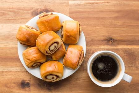 Mini cinnamon buns and coffee. Top view. Stock Photo