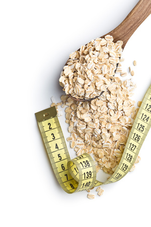 Diet concept. Dry rolled oatmeal and measuring tape. Stock Photo