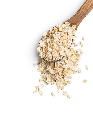 oats: Dry rolled oatmeal in wooden spoon. Isolated on white.