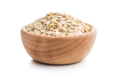 Dry rolled oatmeal in wooden bowl isolated on white background. 免版税图像