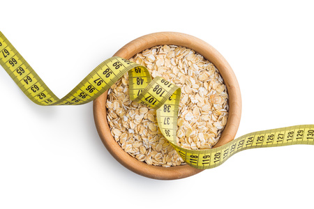 grained: Diet concept. Dry rolled oatmeal and measuring tape. Stock Photo