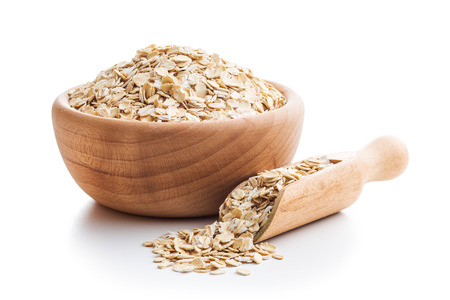 Dry rolled oatmeal in wooden scoop isolated on white background.
