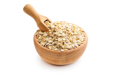 Dry rolled oatmeal in wooden bowl isolated on white background.