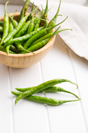 Green chili peppers on white table. Stock Photo