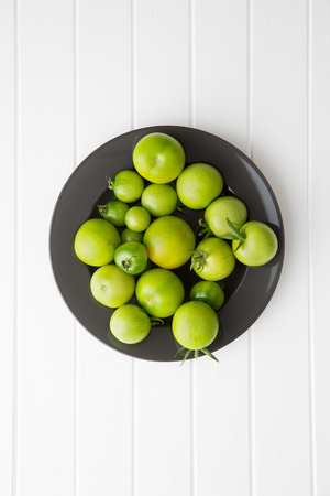 green vegetable: Unripe green tomatoes on kitchen table. Top view. Stock Photo