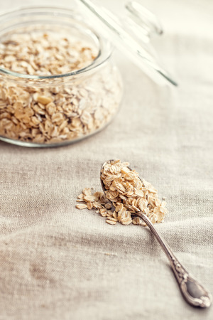 grained: Dry rolled oatmeal in silver spoon.