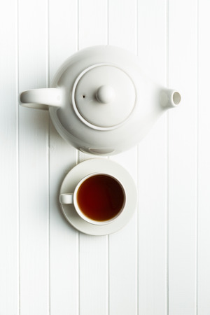 A cup of black tea and teapot on white table. Top view.