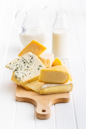 Different kinds of cheeses on white wooden table.